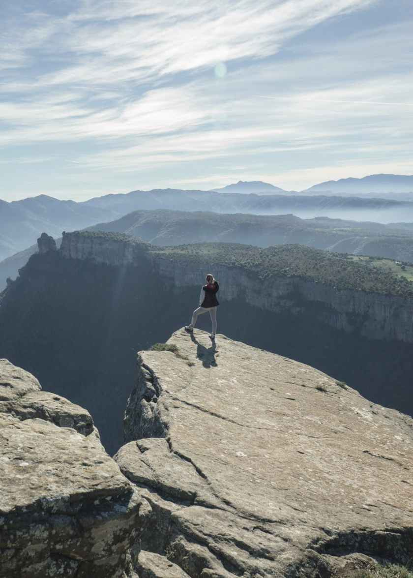 woman standing on mountain cliff
